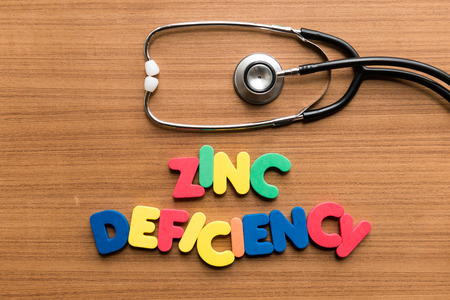 human factors: zinc deficiency colorful word with stethoscope on wooden background