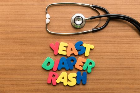 rash: pa�al erupci�n de levadura palabra colorido con el estetoscopio en el fondo de madera