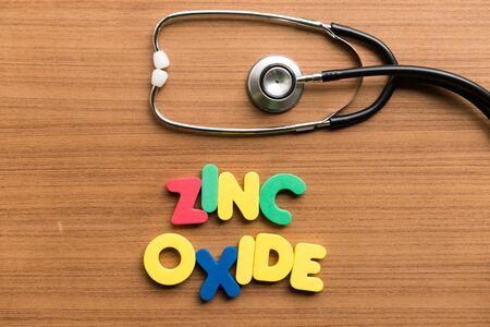 oxide: zinc oxide colorful word with stethoscope on wooden background Stock Photo