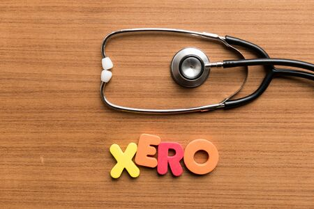 xero colorful word with stethoscope on wooden background