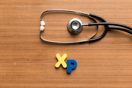 xp: xp colorful word with stethoscope on wooden background Stock Photo