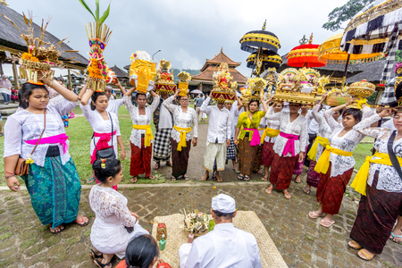 ubud: Bali, Indonesia - December 23, 2016 : Hindu women praying at balinese temple in Bali, Indonesia