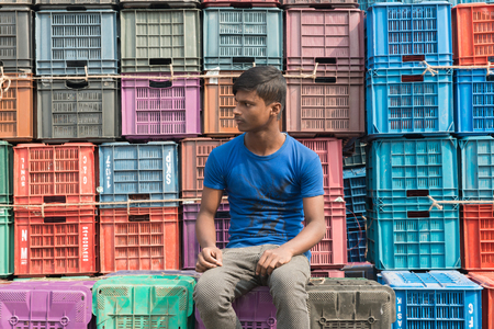 DHAKA, BANGLADESH - December 13: a boy sitting on the roadside on December, 13, 2016 in Dhaka, Bangladesh