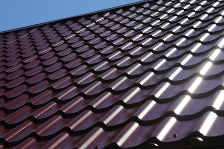 metal shingles on the roof of the house on a Sunny day.