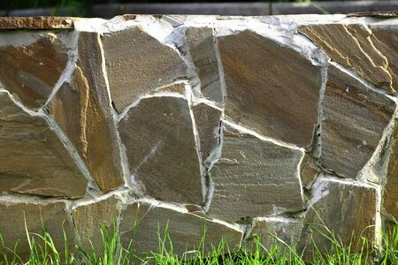 stone wall with grass lit by sunlight