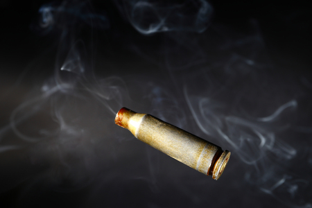 Empty bullet shell casings, on a black background, smoke.