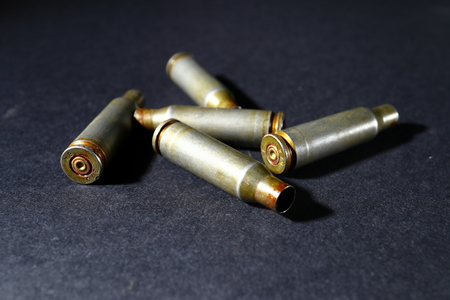 Empty bullet shell casings, on a black background, smoke.