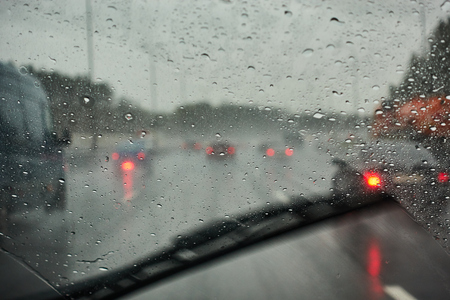 blurred view of road traffic on a rainy day through the car window. raindrops on the glass window of the car.