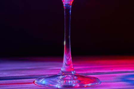 Glass stem on wooden table and black background.
