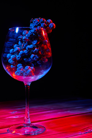 A bunch of ripe grapes in a glass glass glass on a wooden table and a black background. 스톡 콘텐츠