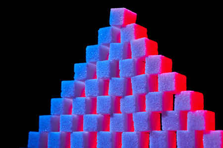A composition of sugar cubes illuminated with multicolored light sources.