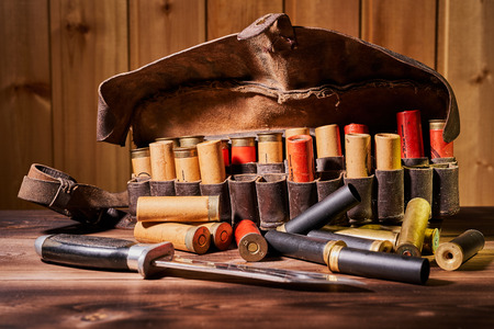 Old hunting cartridges and bandoleer on a wooden table.