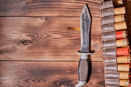 Old hunting cartridges, a knife and a clip on a wooden table. Imagens - 113081148