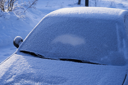 The car is covered with snow. Bad weather in winter.