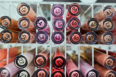 Decorative cosmetics samples, testers. Various lip pencils in a showcase of beauty shop. Retail, shopping.