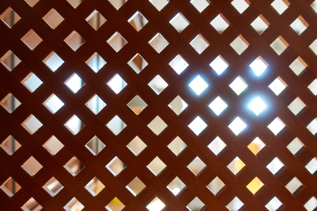 Decorative wooden lattice. Wooden background with light source at the back. Banco de Imagens
