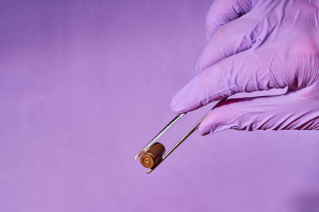 Man's gloved hand with tweezers and bullet casing.