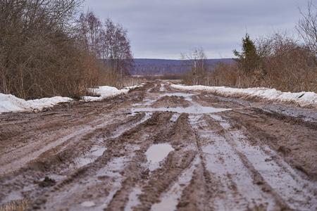 Strada sterrata rotta con pozzanghere all'inizio della primavera.