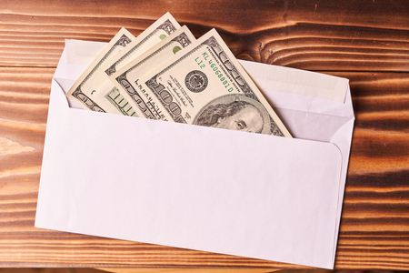 American dollars in a white envelope. Wooden background.