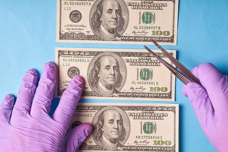 Men's hands in gloves holding unfolded dollars. Banco de Imagens