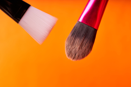 Makeup brushes on orange background. Tools for cosmetic procedures.