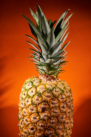 Ripe pineapple on orange background. Close-up shooting. Stock Photo