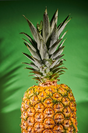 Ripe pineapple on green background. Close-up shooting.