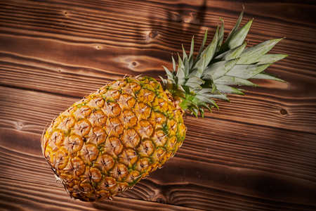 Ripe pineapple on wood background. Close-up shooting.