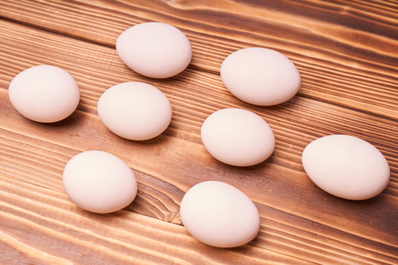 Chicken eggs laid on a wooden table.
