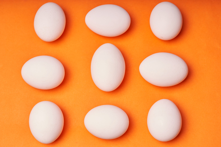 Chicken eggs laid out on an orange background.
