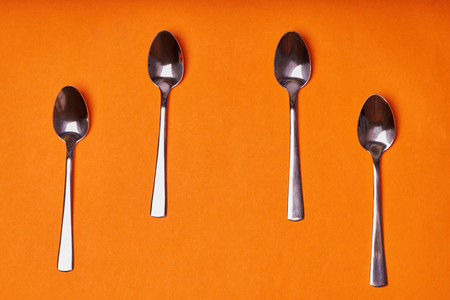 four teaspoons laid out on an orange background.