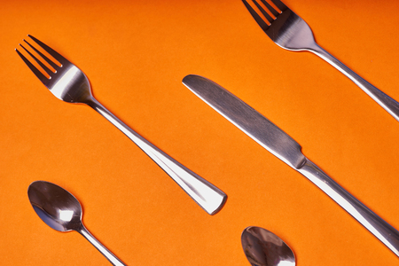 knives, spoons and forks laid out on an orange background.
