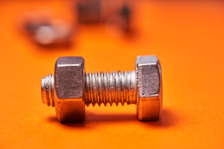 Bolted connecting elements on orange background close-up.