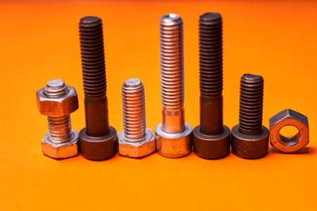 Bolted connecting elements on orange background close-up. Stock Photo