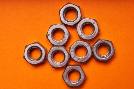 hex nuts on orange background. Bolted connection elements. Stock Photo