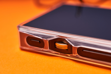 Portable music player on orange background close-up.