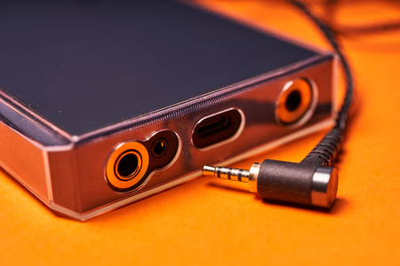 Portable music player on orange background with wire.