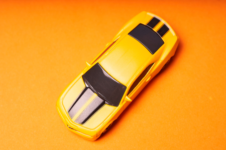 Yellow toy car on orange background close-up.