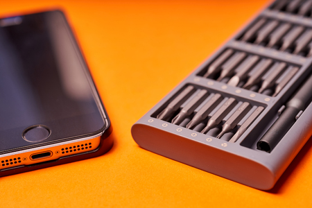 Set of miniature bits for screwdrivers and phone on an orange background.