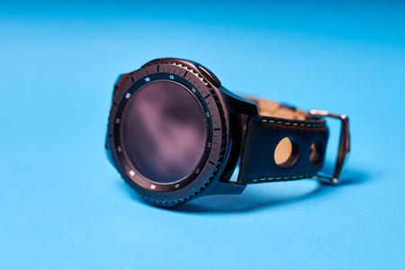 Modern electronic smart watch on blue background.