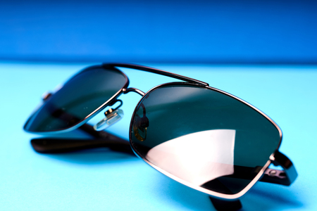 Sunglasses in metal frame with grey lenses on blue background.