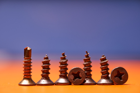 Screws close-up on a colored background. Fastening element. Stock Photo