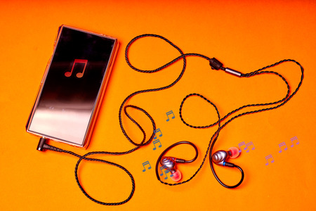 Portable music player on orange background with earphones and wire. Stock Photo