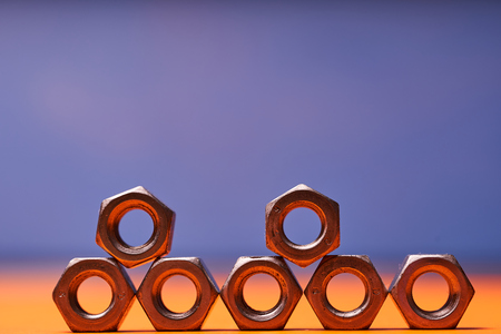 Bolted connecting elements on orange, blue background close-up. Stock Photo