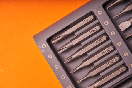 A set of miniature bits for the screw driver on orange background.