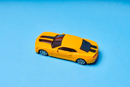 Yellow toy car on blue background close-up.