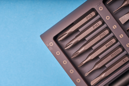 A set of miniature bits for the screw driver on blue background. Stock Photo