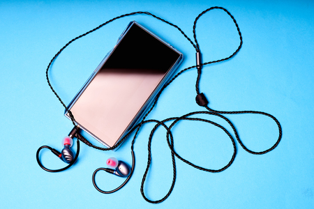 Portable music player on blue background with earphones and wire.