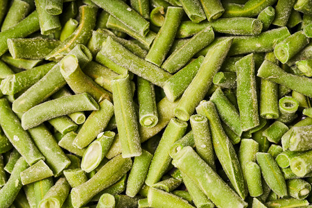 Chopped green bean pods, covered with ice. Stock Photo