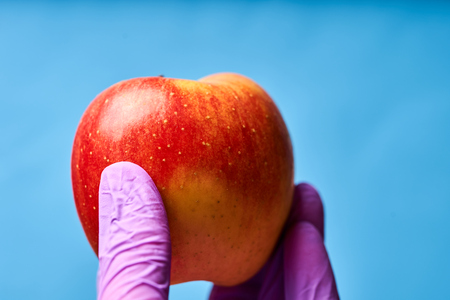Mans hand in a glove holding an Apple. Blue background.
